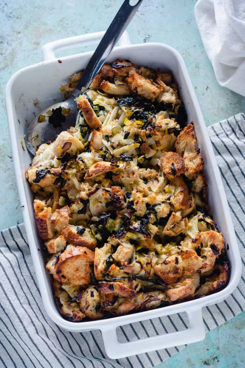 Fennel and Kale Stuffing in a baking dish with a serving spoon