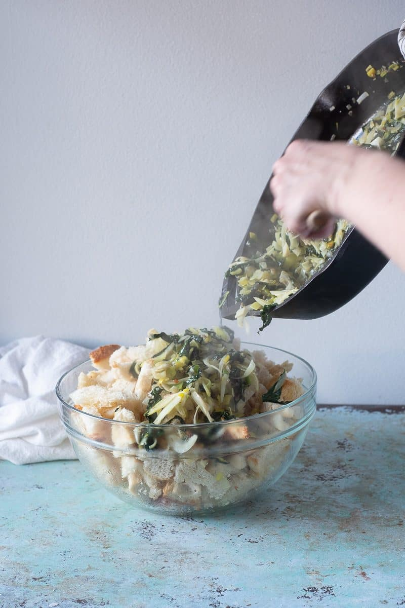 Adding vegetable mixture to bread pieces in a bowl