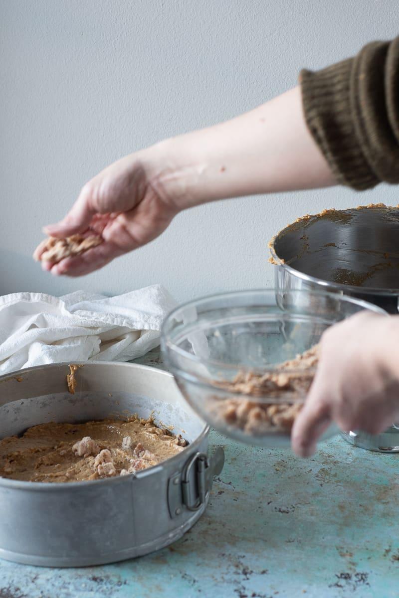 Sprinkling pecan streusel over the pumpkin coffee cake