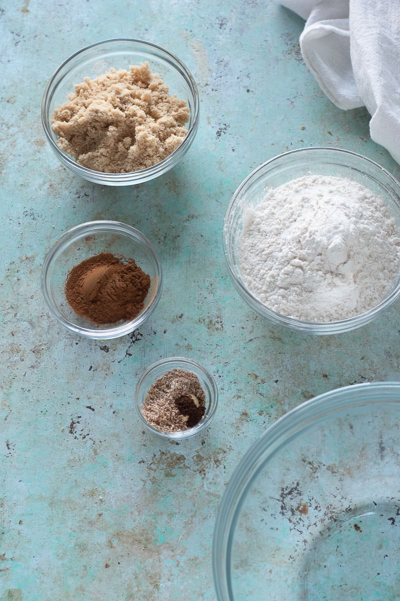 Spices in bowls, brown sugar in a bowl, flour in a bowl