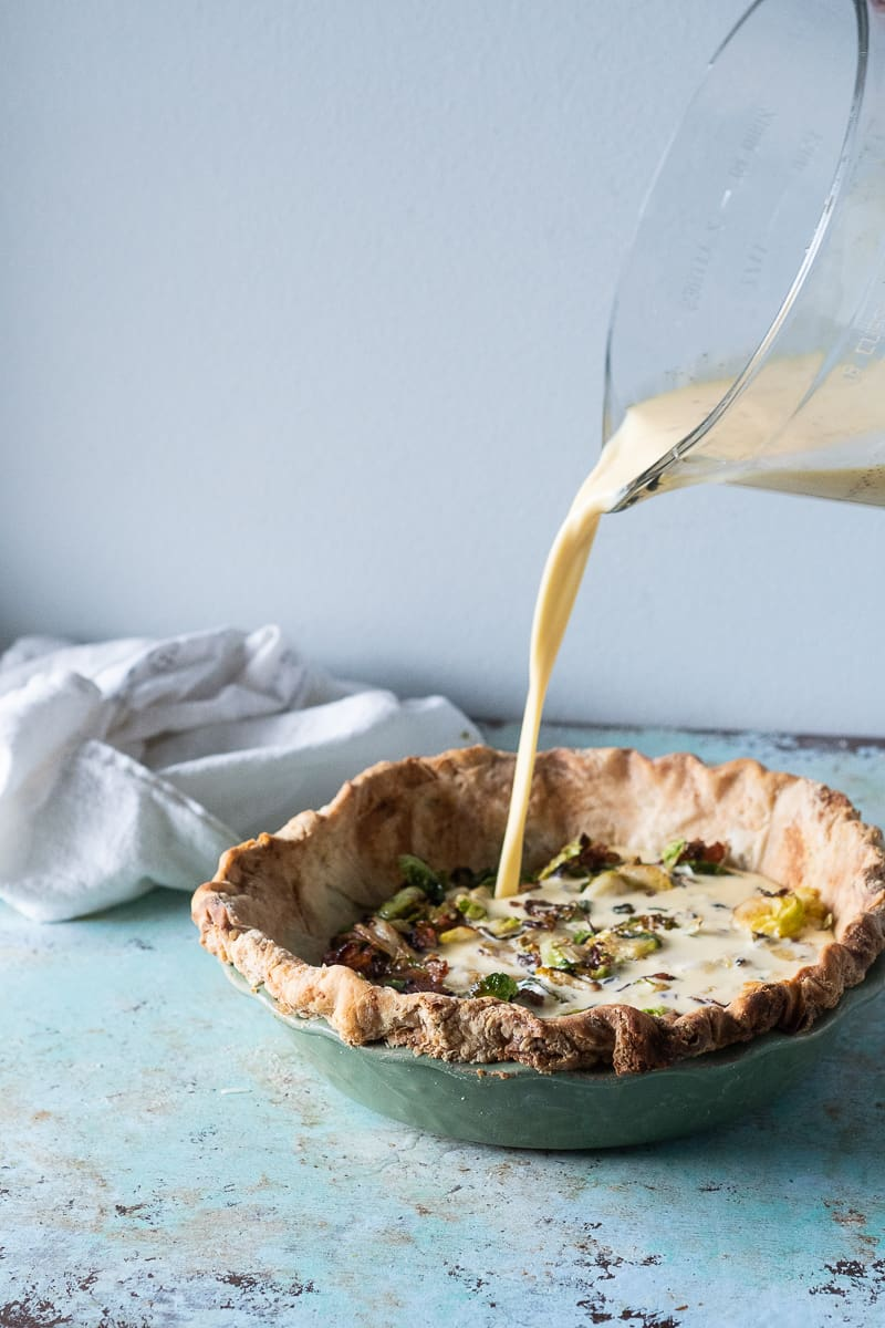 Pouring custard filling over bacon and Brussels sprouts into a pie crust
