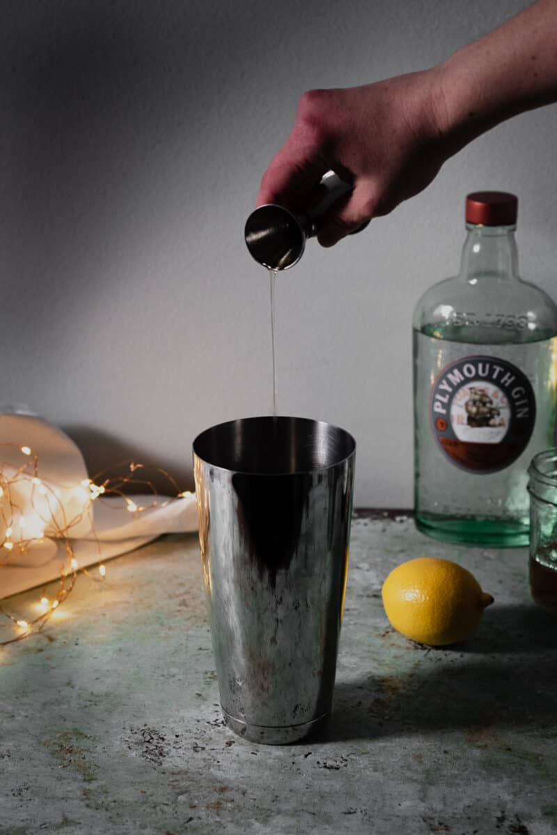 Hand pouring gin into cocktail shaker