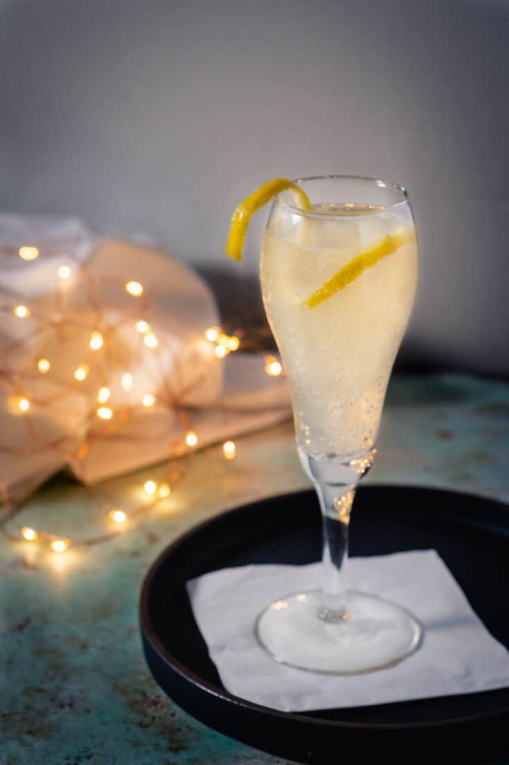 French 75 cocktail in a glass with a lemon garnish with twinkling lights behind it