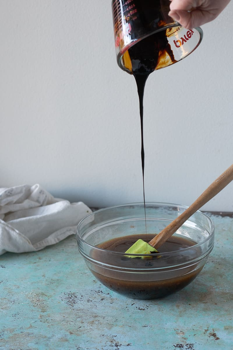 Pouring molasses into the bowl of wet ingredients