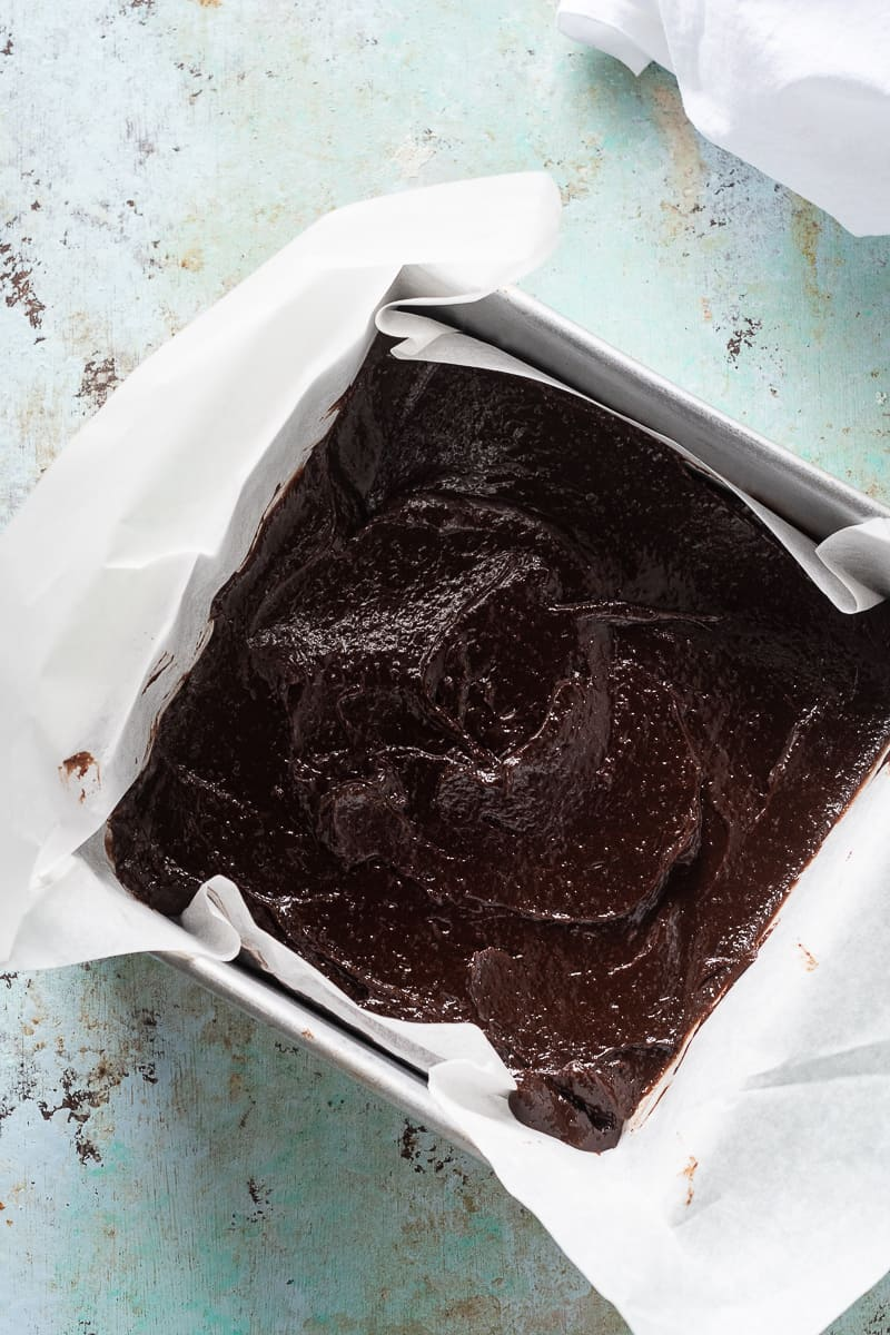 Brownie batter in a parchment-lined pan