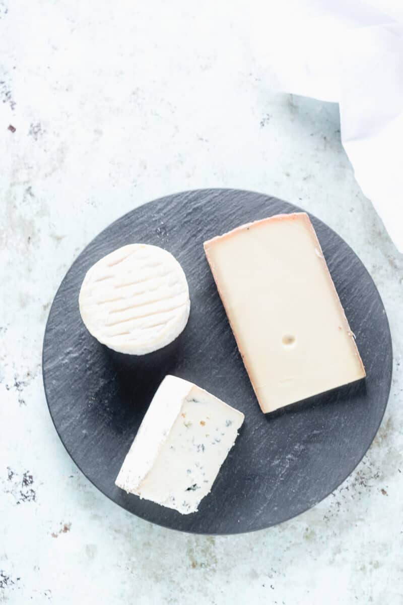 A triple creme cheese, a wedge of semi-hard cheese, and a wedge of blue cheese