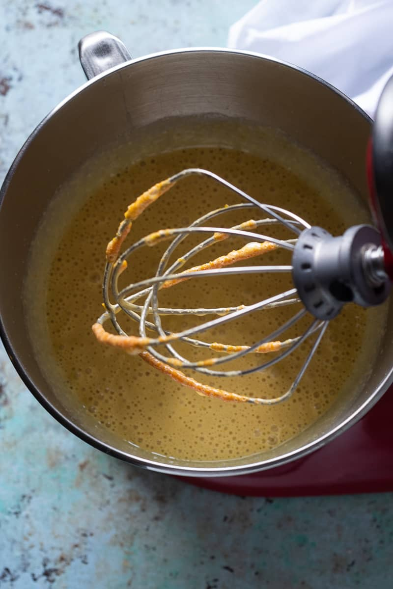 Whisk attachment of a stand mixer over orange cake batter