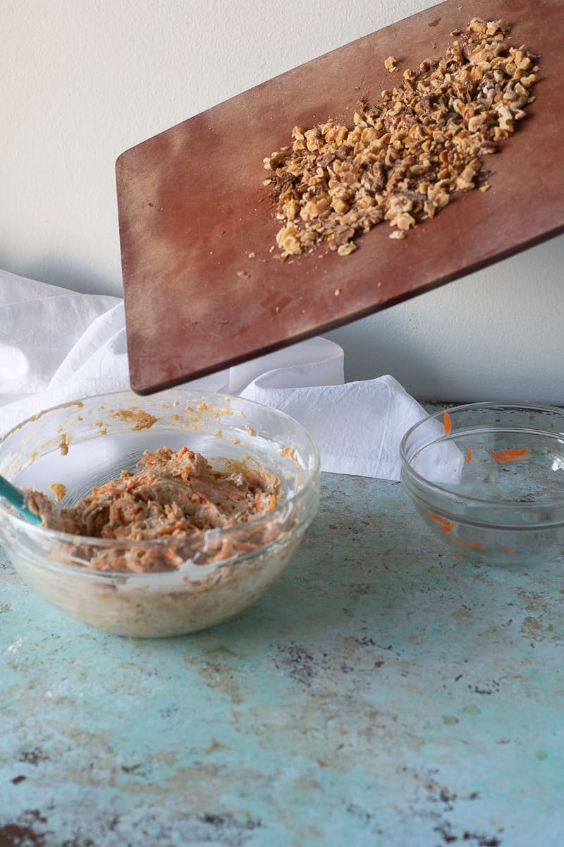 Adding toasted walnuts to the carrot cake batter
