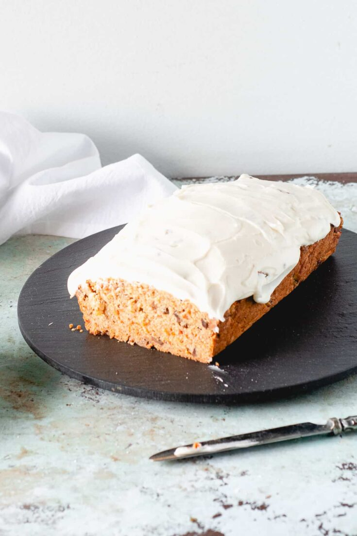 Carrot Loaf Cake with Cream Cheese Frosting, with slice removed to expose crumb