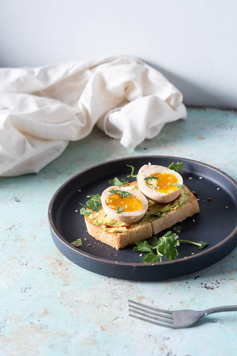 Ramen eggs on avocado toast with sriracha and herbs