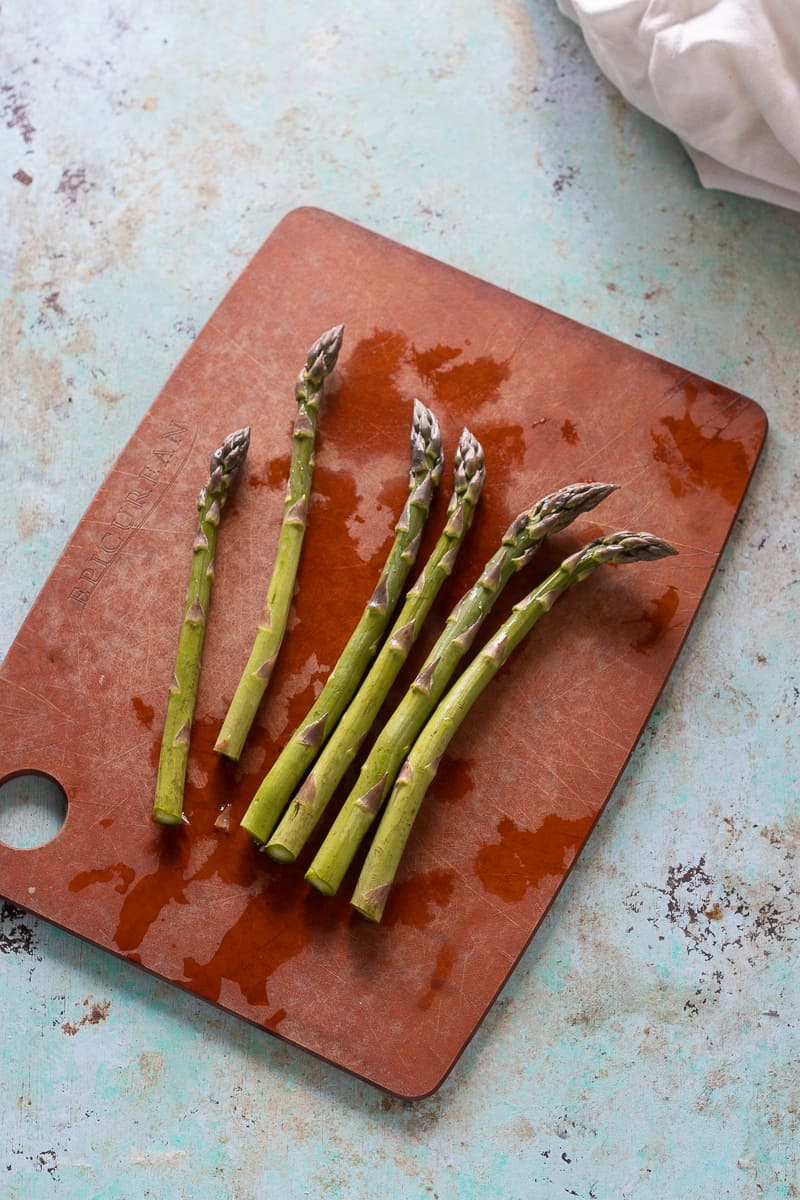 Asparagus spears, trimmed, on a cutting board