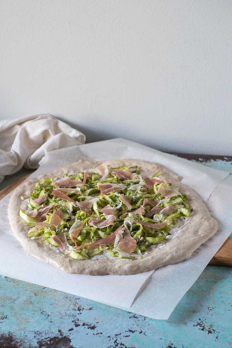 Prosciutto and shaved asparagus on unbaked pizza dough on parchment paper on a wooden pizza peel