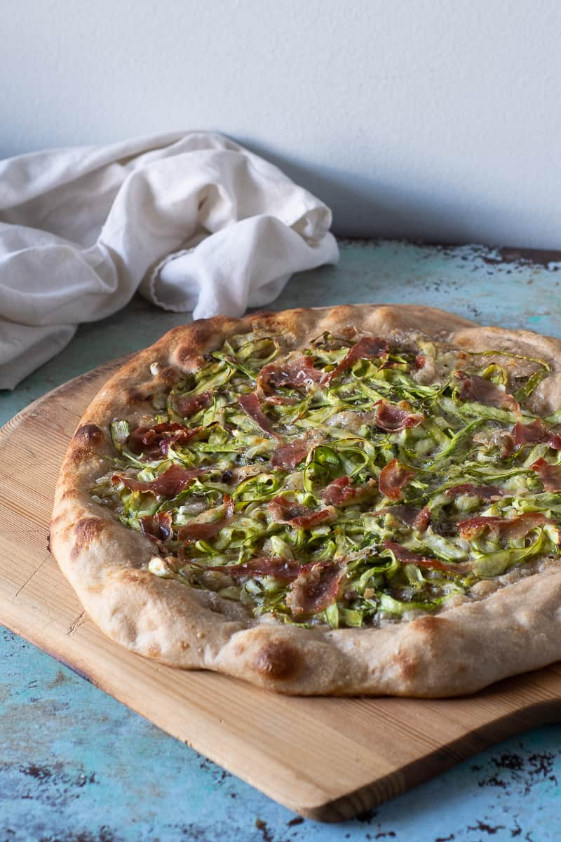 Asparagus Pizza with Prosciutto on a wooden peel, side view