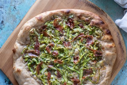 Asparagus Pizza with Prosciutto on a wooden peel