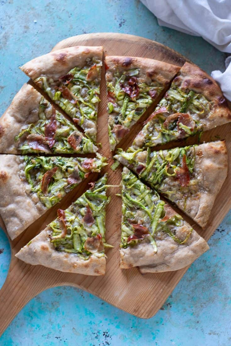 Sliced asparagus and prosciutto pizza on a wooden peel