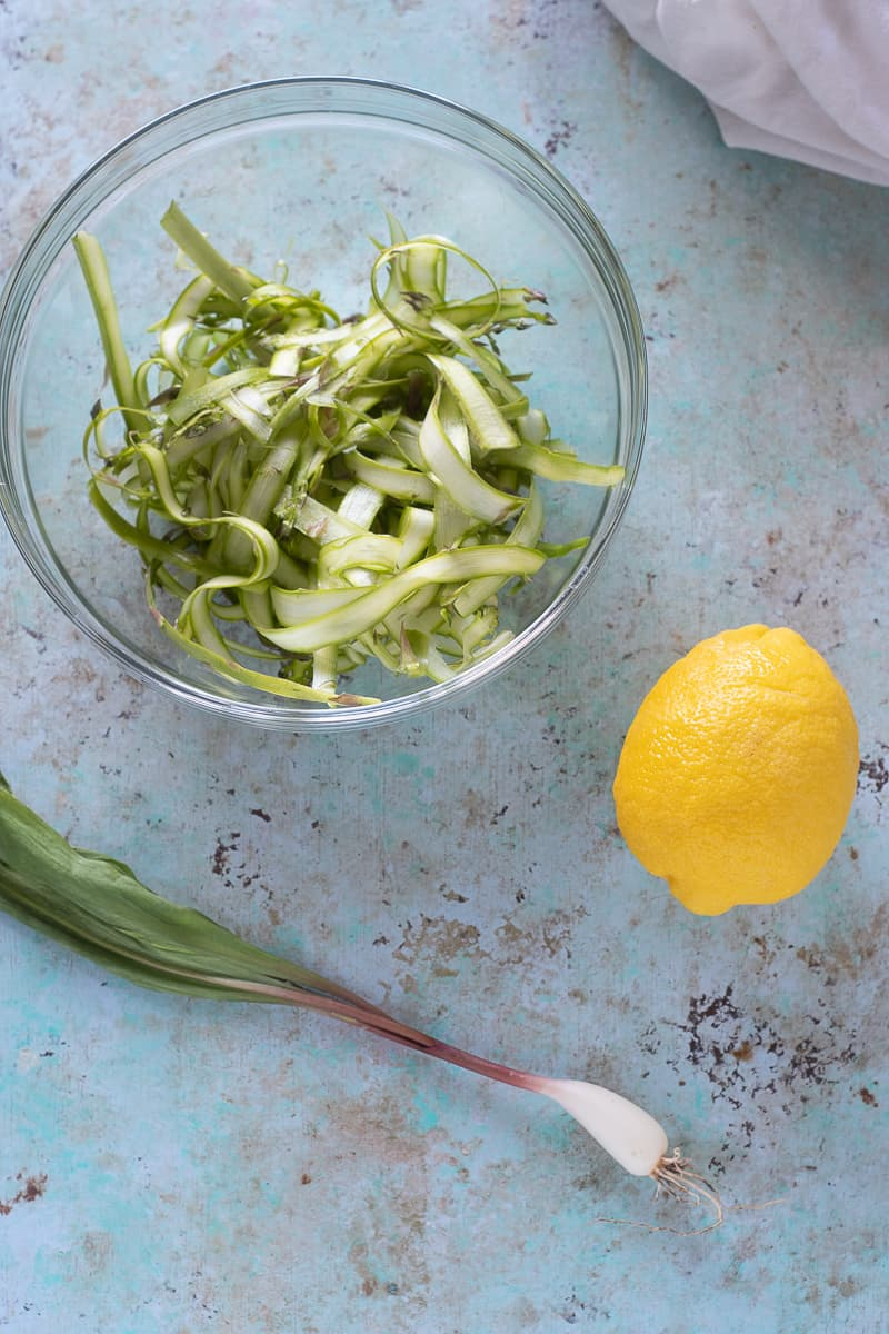 Shaved asparagus in a bowl, a lemon, and a ramp (wild onion)