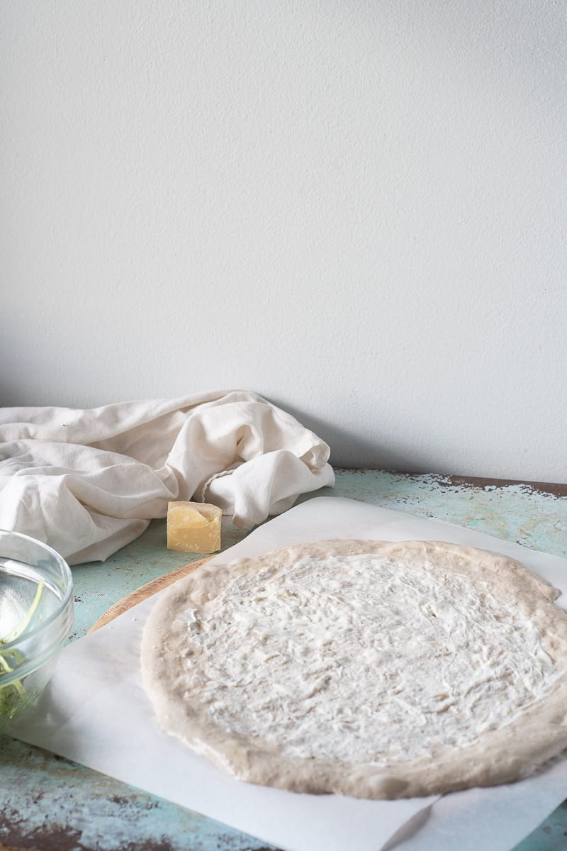 Unbaked pizza dough stretched out and smeared with crème fraîche