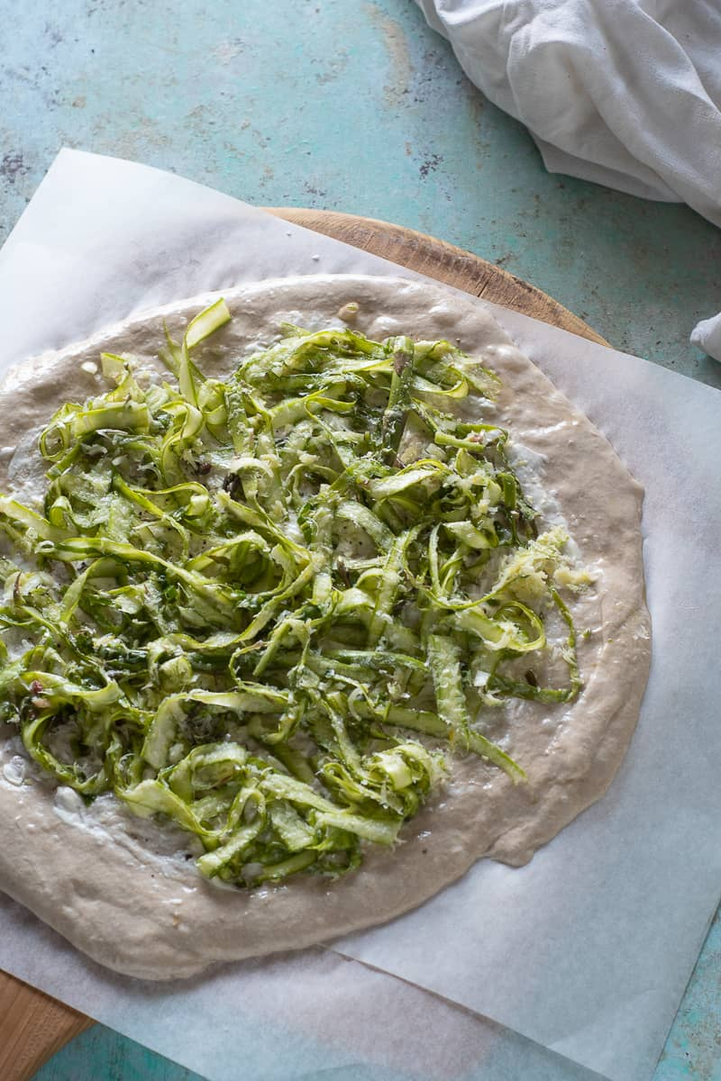 Shaved asparagus on unbaked pizza dough on parchment paper