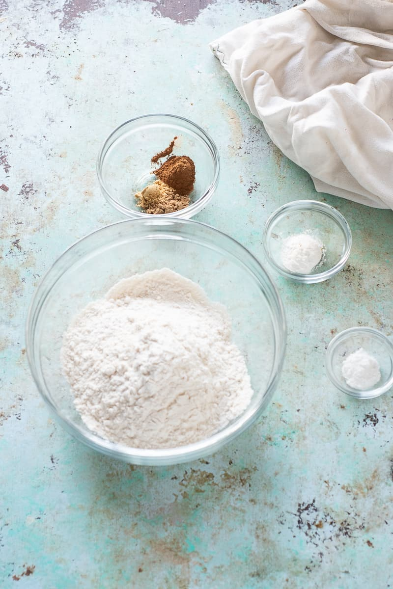 Flour in a bowl next to bowls of baking powder, baking soda, and cinnamon, coriander, and ginger