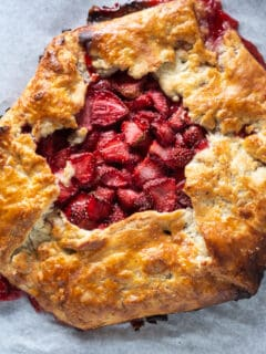 Strawberry galette on parchment paper on a sheet pan, overhead shot