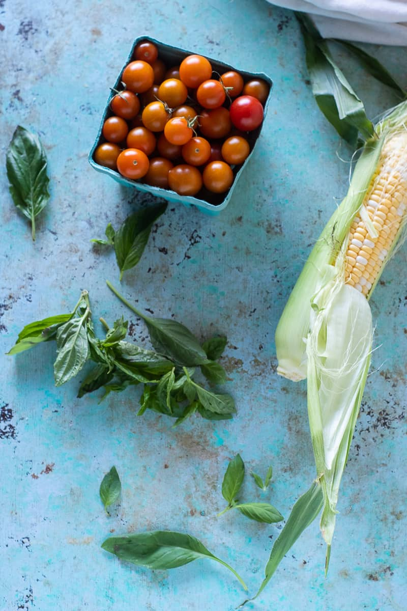 Pint of sungold tomatoes, ear of corn partially shucked, basil leaves on a table