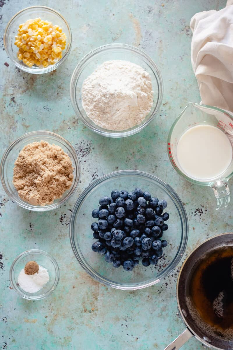 Bowls of sweet corn kernels, flour, whole milk, blueberries, brown sugar, baking soda, salt, and coriander