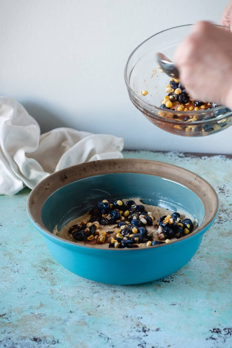Hand spooning sweet corn and blueberry topping over the spoon cake batter