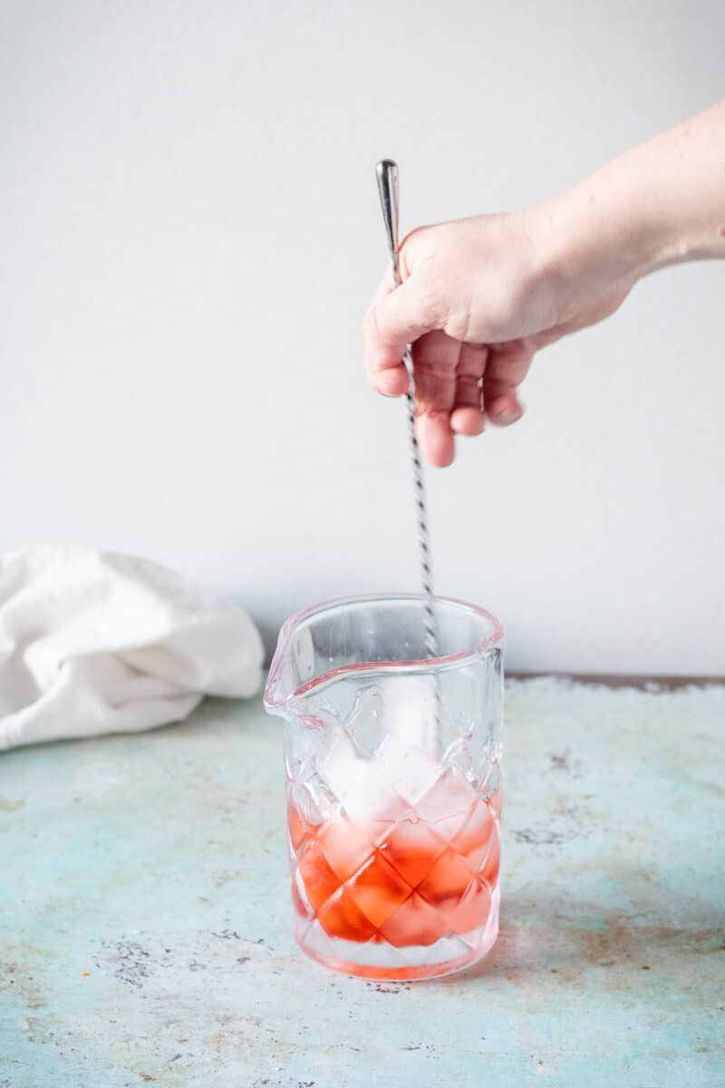 Hand stirring a Negroni in a mixing glass with a long cocktail spoon