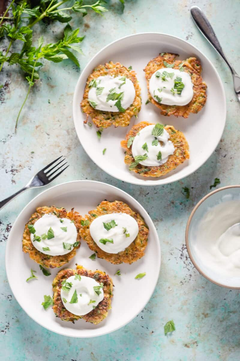 Two plates of zucchini fritters topped with yogurt and mint
