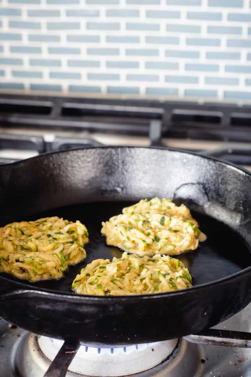 Zucchini fritters in a cast iron pan, raw side up