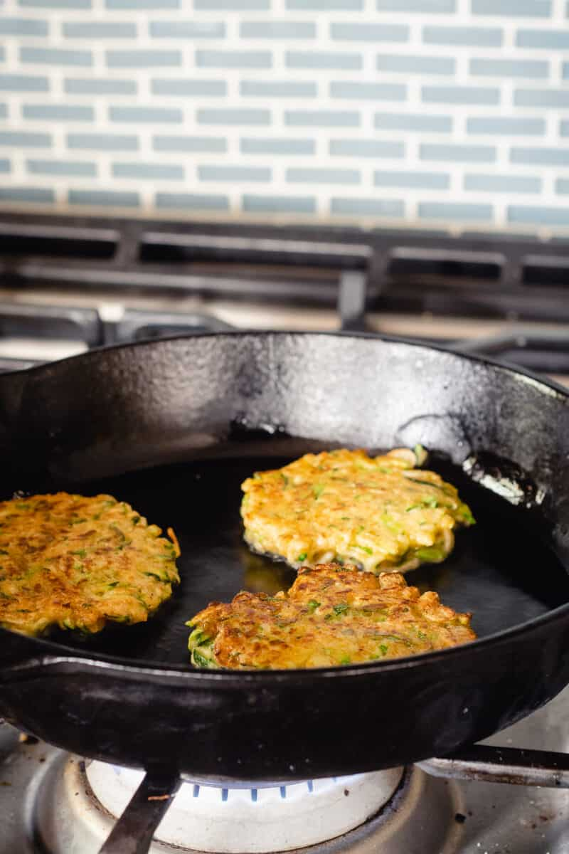 Zucchini fritters in a cast iron pan, cooked side up