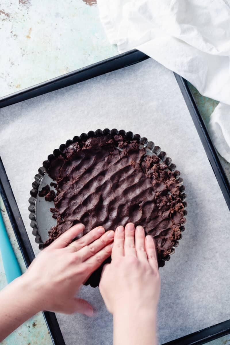 Hands pressing the chocolate tart dough into the tart pan