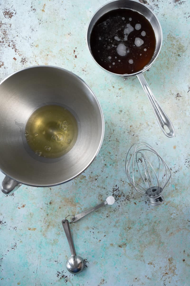 Meringue and sugar syrup in bowls, cream of tartar in a measuring spoon