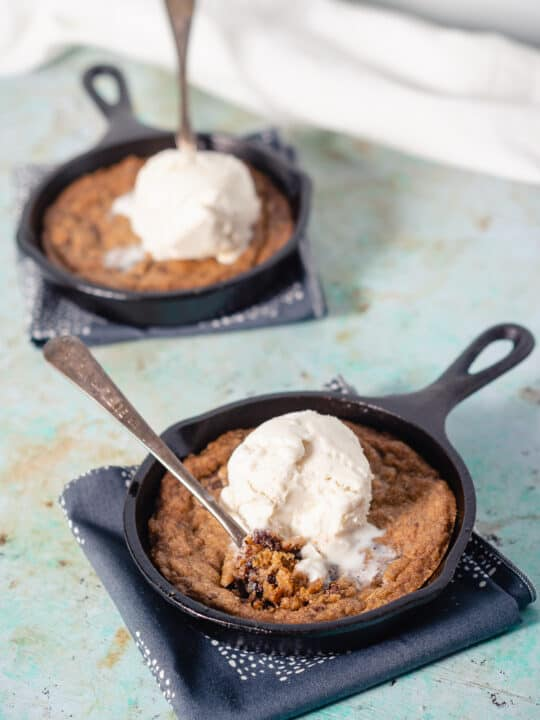 Two mini chocolate chip skillet cookies topped with vanilla ice cream