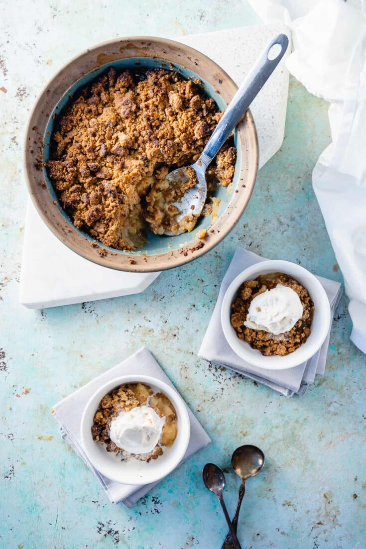 Apple crisp with two bowls with ice cream