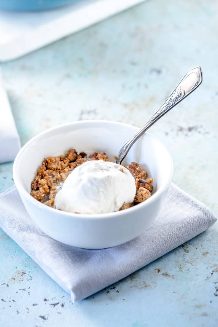 A bowl of apple crisp topped with vanilla ice cream