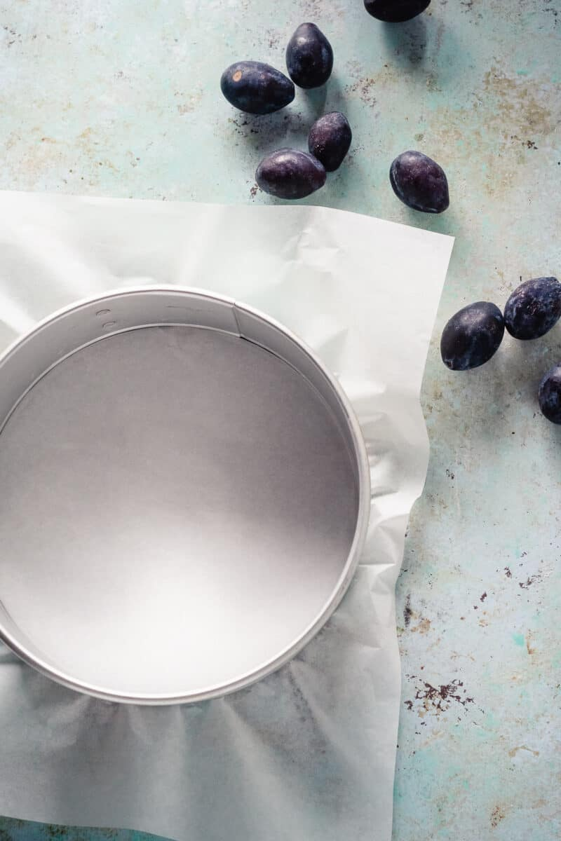 Cake pan lined with parchment paper and plums nearby