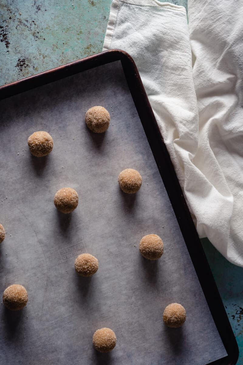 Balls of cookie dough coated in sugar on a baking sheet