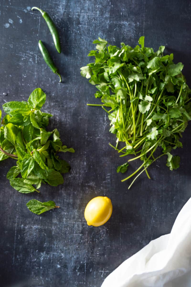 Mint, serrano peppers, cilantro, and lemon on a counter