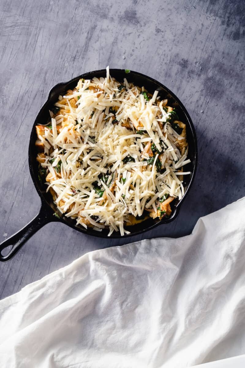 Unbaked chard and gruyere strata in a cast iron pan