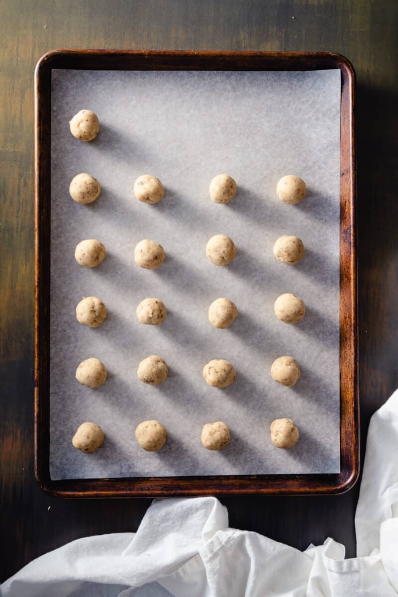 Cookie dough rolled into balls and arranged on a sheet pan