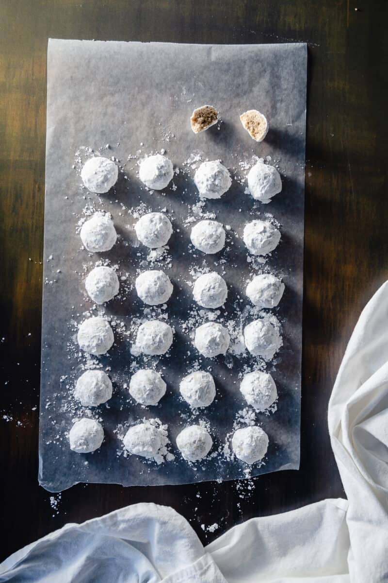 Mexican Wedding Cookies lined up on a sheet of wax paper