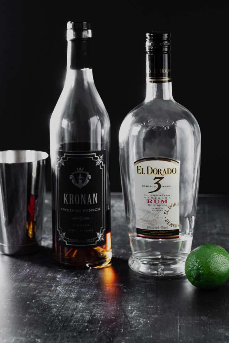 A mixing tin, a bottle of Swedish Punsch, a bottle of light rum