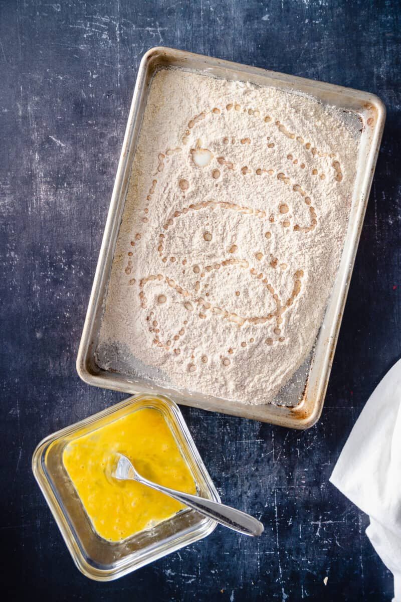 Flour and cornmeal breading mixture with a dish of whisked egg nearby