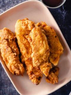 Crispy Chicken Tenders on a pink plate