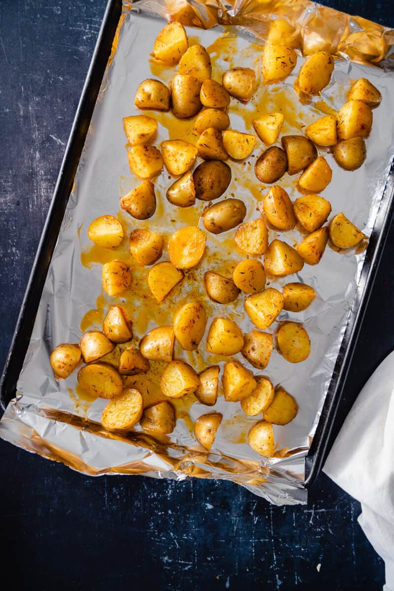 Oiled and seasoned potatoes on a foil-lined sheet pan