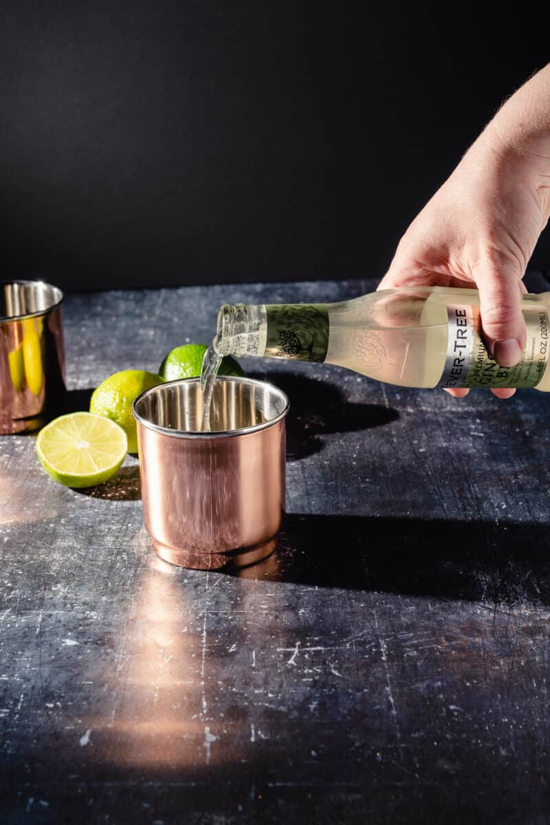 Ginger beer being poured into a copper cup to make a Moscow Mule