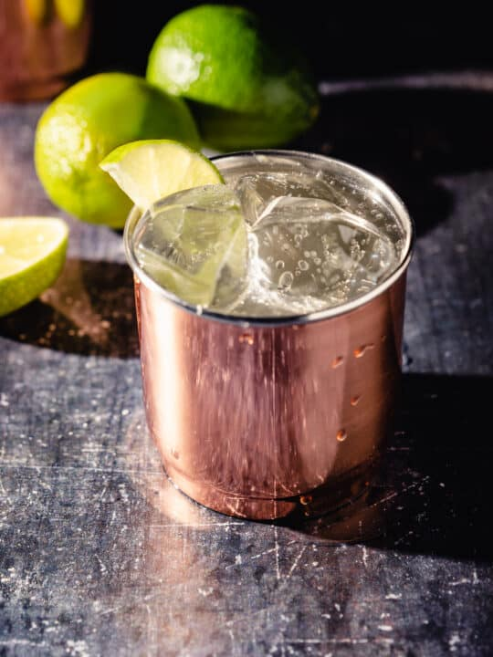 Moscow Mule cocktail in a copper tumbler with limes in the background
