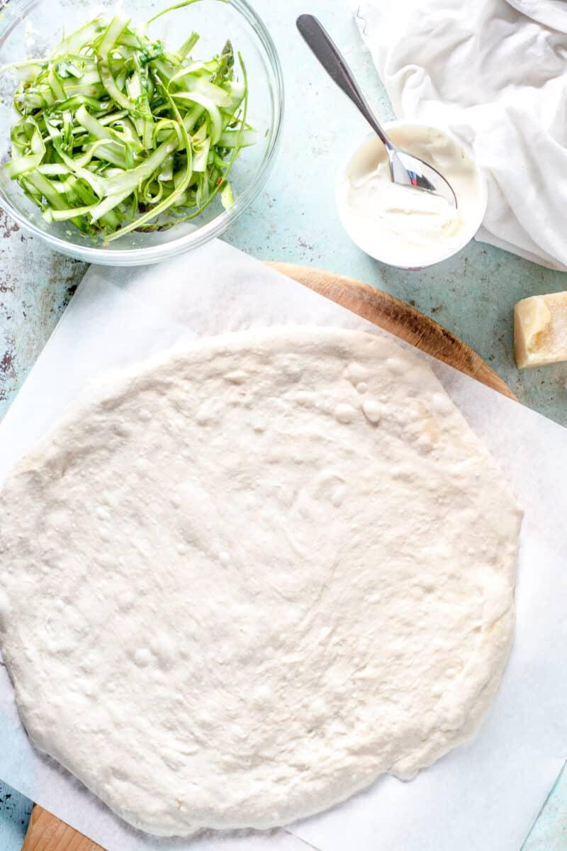 Shaved asparagus in a bowl, creme fraiche, pizza dough on parchment paper