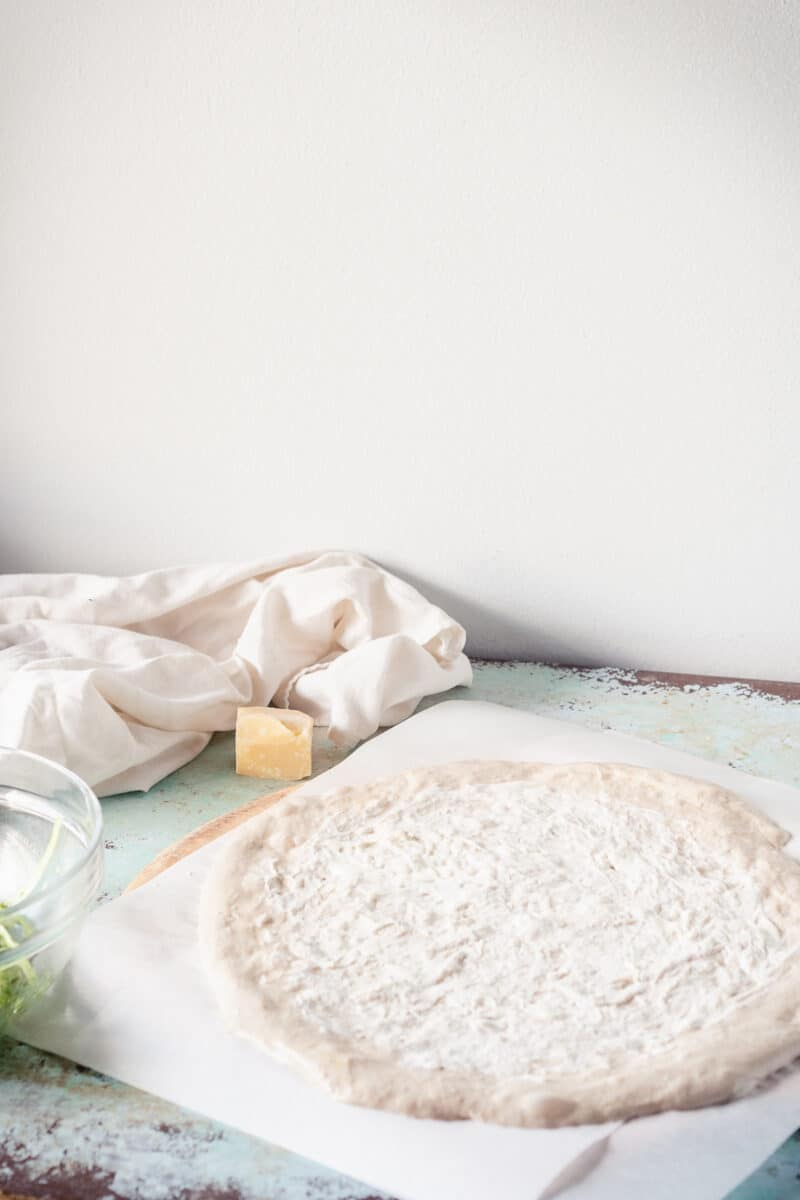 Pizza dough with a thin layer of creme fraiche